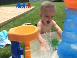 Jack loves splashing at the water table.